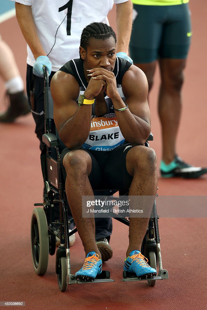 <a gi-track='captionPersonalityLinkClicked' href=/galleries/search?phrase=Yohan+Blake&family=editorial&specificpeople=2172755 ng-click='$event.stopPropagation()'>Yohan Blake</a> of Jamaica is led off in a wheelchair after going down with an injury in the Mens 100m final during the IAAF Diamond League Day 1 at Hampden Park on July 11, 2014 in Glasgow, Scotland.