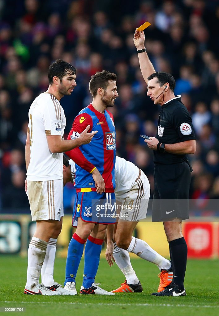Yohan Cabaye (C) of Crystal Palace is shown a yellow card by referee Neil Swarbrick (R) during the Barclays Premier League match between Crystal Palace and Swansea City at Selhurst Park on December 28, 2015 in London, England.