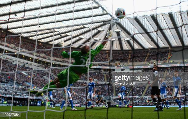Yohan Cabaye of Newcastle United beats Wigan Athletic keeper Ali Al Habsi to score the first goal during the Barclays Premier League match between...