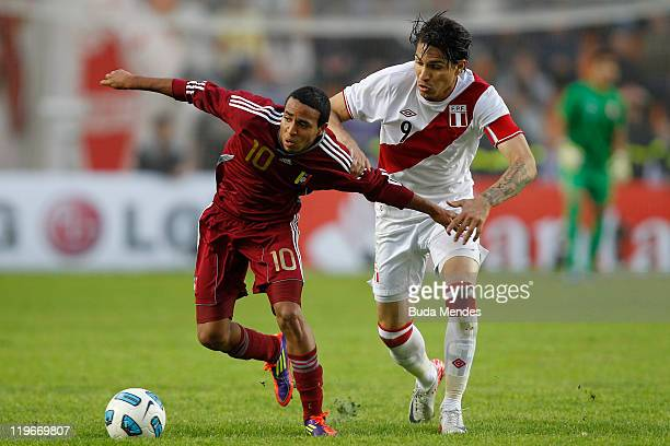 Yohandry Orozco of Venezuela struggles for the ball with Jose Paolo Guerrero of Peru during the Copa America 2011 third place match between Venezuela...
