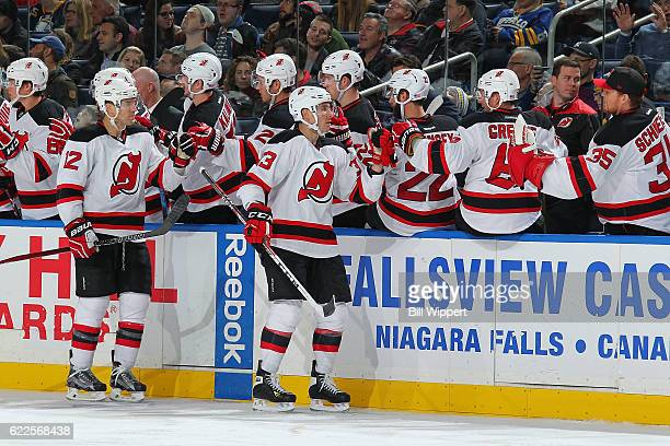Yohann Auvitu of the New Jersey Devils celebrates his first career NHL goal against the Buffalo Sabres with teammates during an NHL game at the...