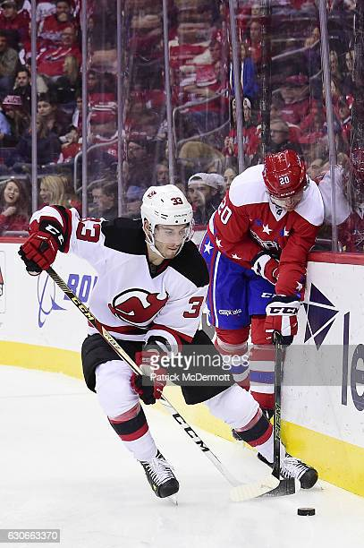 Yohann Auvitu of the New Jersey Devils controls the puck against Lars Eller of the Washington Capitals in the third period during a NHL game at...