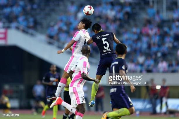 Yohei Toyoda of Sagan Tosu and Kazuhiko Chiba of Sanfrecce Hiroshima compete for the ball during the JLeague J1 match between Sanfrecce Hiroshima and...