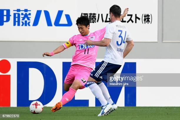 Yohei Toyoda of Sagan Tosu takes on Milos Degenek of Yokohama FMarinos during the JLeague J1 match between Sagan Tosu and Yokohama FMarinos at Best...