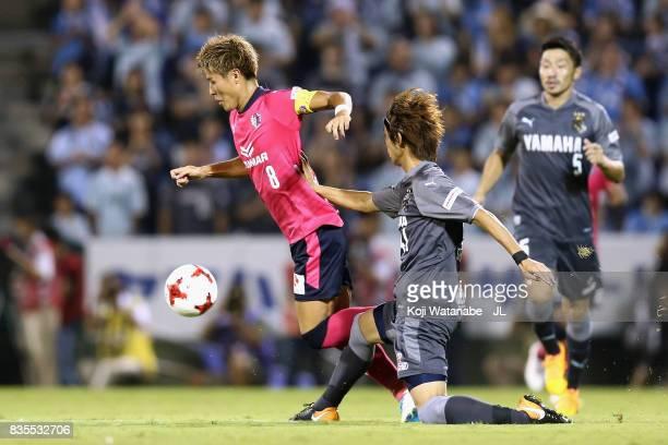 Yoichiro Kakitani of Cerezo Osaka is tackled by Shohei Takahashi of Jubilo Iwata during the JLeague J1 match between Jubilo Iwata and Cerezo Osaka at...