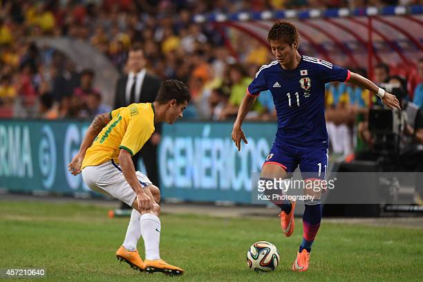 Yoichiro Kakitani of Japan keeps the ball under the pressure from Philippe Coutinho of Brazil during the international friendly match between Japan...