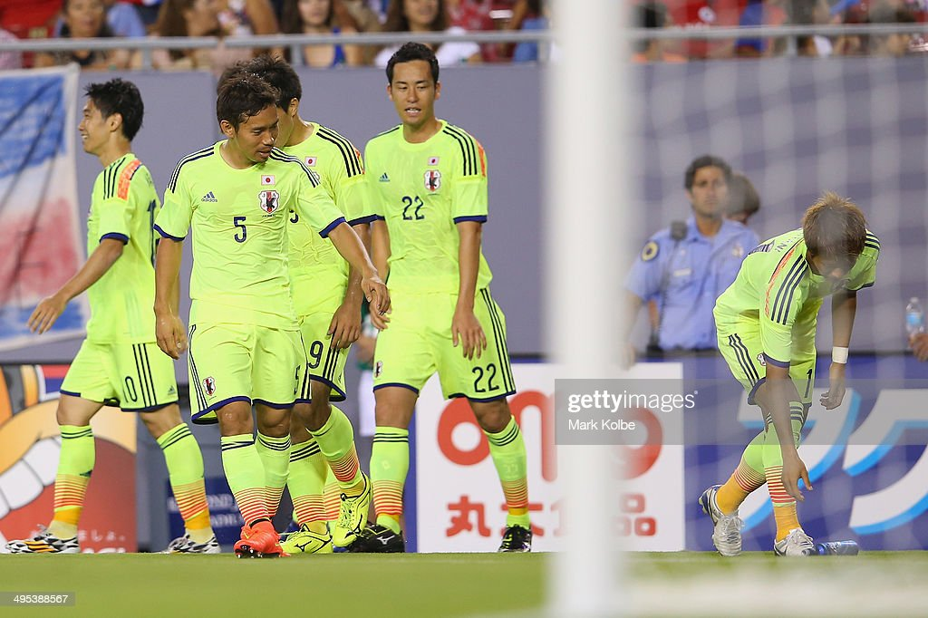 Yoichiro Kakitani of Japan picks up a bottle thrown onto the field as Shinji Kagawa of Japan celebrated with his team mates after scoring a goal during the International Friendly Match between Japan and Costa Rica at Raymond James Stadium on June 2, 2014 in Tampa, Florida.
