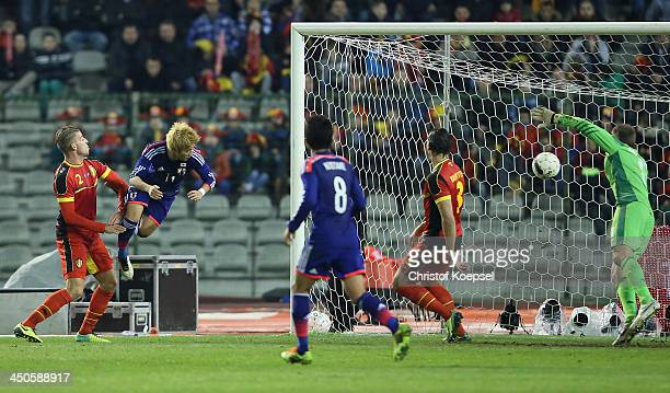 Yoichiro Kakitani of Japan scores the first goal againts Toby Alderweireld of Belgium Daniel van Buyten and Simon Mignolet of Belgium during the...