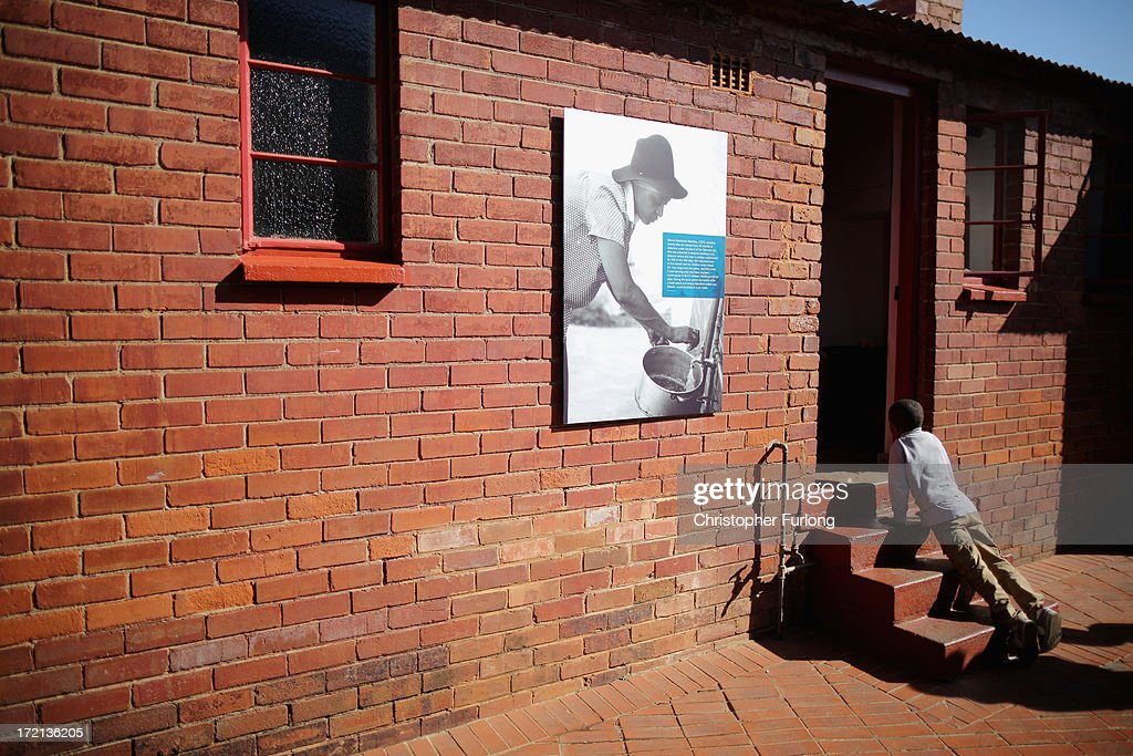 A yoing boy peers through the back door of the 'Mandela House' museum at 8115 in Vilakazi Street in the Orlando West section of Soweto Township on July 2, 2013 in Soweto, Johannesburg, South Africa. 8115 is the location of the first house owned by former South African President Nelson Mandela where he lived for 44 years from 1946 to 1990. The 'Mandela House', now a museum is managed by the Soweto Heritage Trust which has seen an increase in vistors both local and international since Mandela was hospitalized with a lung infection on June 8, 2013 and still remains in a critcal condition.