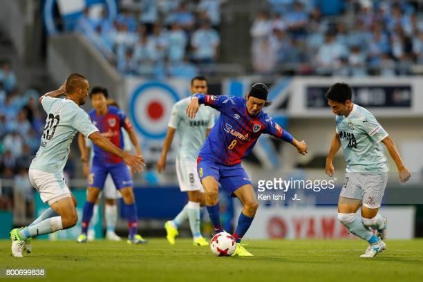 Yojiro Takahagi of FC Tokyo competes for the ball against Kengo Kawamata and Hayao Kawabe of Jubilo Iwata during the JLeague J1 match between Jubilo...