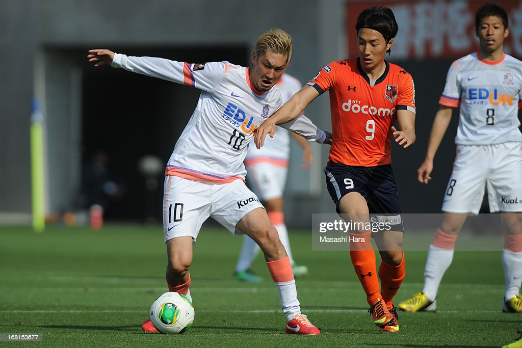 Yojiro Takahagi #10 of Sanfrecce Hiroshima (L) and Cho Young Cheol #9 of Omiya Ardija compete for the ball during the J.League match between Omiya Ardija and Sanfrecce Hiroshima at Nack 5 Stadium Omiya on May 6, 2013 in Saitama, Japan.