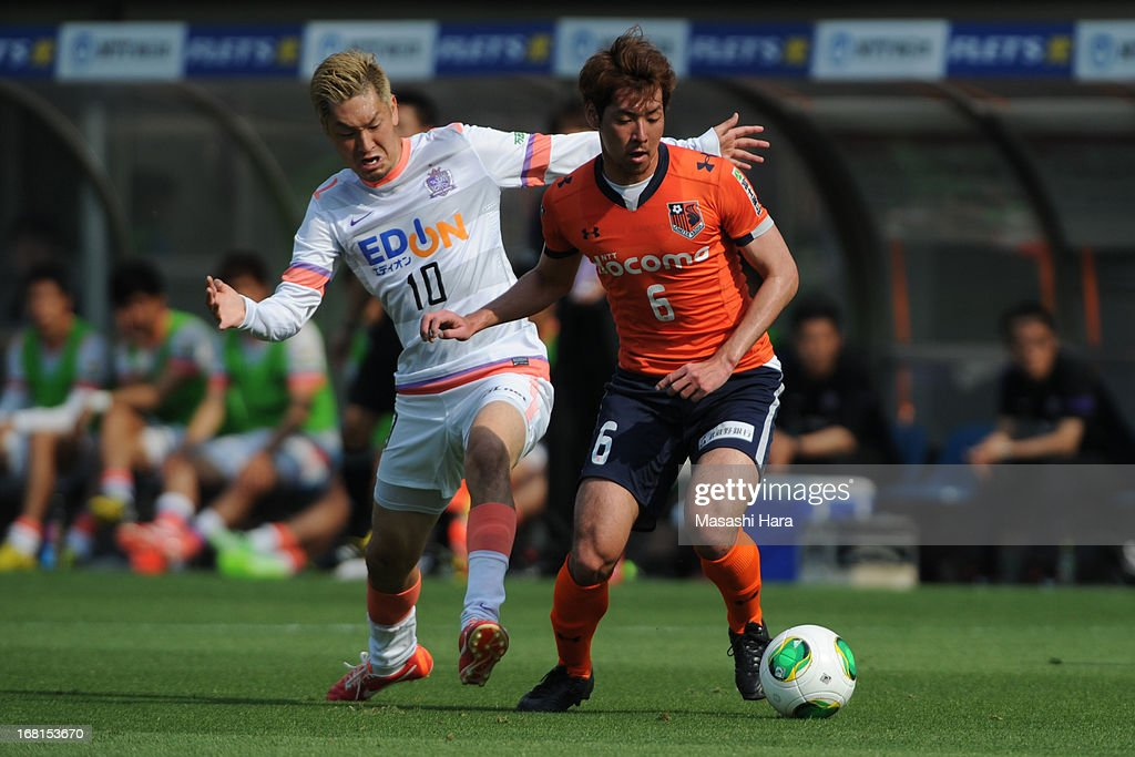 Yojiro Takahagi #10 of Sanfrecce Hiroshima (L) and Takuya Aoki #6 of Omiya Ardija compete for the ball during the J.League match between Omiya Ardija and Sanfrecce Hiroshima at Nack 5 Stadium Omiya on May 6, 2013 in Saitama, Japan.
