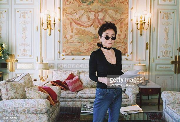 Meeting Plan de face de Yoko ONO souriante un document entre les mains dans sa suite de l'hôtel Ritz à PARIS regardant pardessus ses lunettes noires...