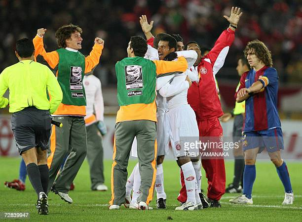 Spain's FC Barcelona captain Carlos Puyol leaves the pitch as players of Brazil's SC Internacional celebrate their victory in the final of the FIFA...