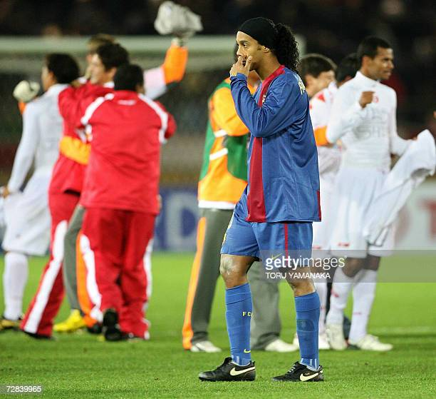Spain's FC Barcelona forward Ronaldinho of Brazil walks past players of Brazil's SC Internacional after the final of the FIFA Club World Cup in...