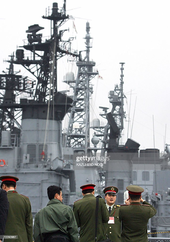 Chinese military servicemen take pictures with ships of the Japanese Maritime SelfDefense docked at Yokosuka base in Kanagawa Prefecture south of...