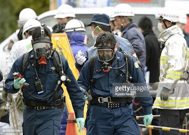 Yokosuka Japan Investigators wearing masks examine a sewer work site around a manhole in the Kurihama district in the city of Yokosuka Kanagawa...
