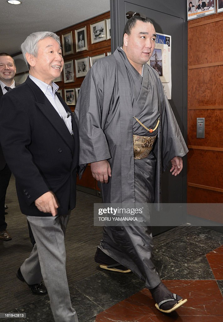 'Yokozuna', or grand champion, Harumafuji of Mongolia (R) is escorted to a press conference at the Foreign Correspondents' Club in Tokyo on February 18, 2013. Harumafuji, a relative lightweight at only 133 kilogrammes (293 pounds), was promoted to the top rank of the sport -- yokozuna -- last September, joining his compatriot Hakuho who had been the lone grand champion for three years. AFP PHOTO / Toru YAMANAKA