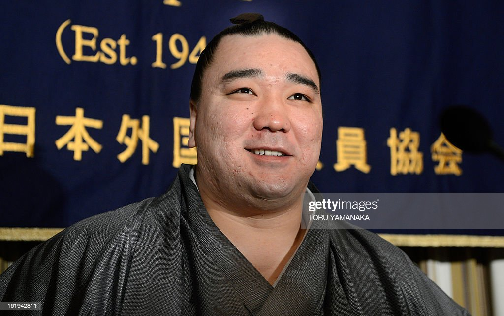 'Yokozuna', or grand champion, Harumafuji of Mongolia smiles for photographers at the start of a press conference at the Foreign Correspondents' Club in Tokyo on February 18, 2013. Harumafuji, a relative lightweight at only 133 kilogrammes (293 pounds), was promoted to the top rank of the sport -- yokozuna -- last September, joining his compatriot Hakuho who had been the lone grand champion for three years. AFP PHOTO / Toru YAMANAKA