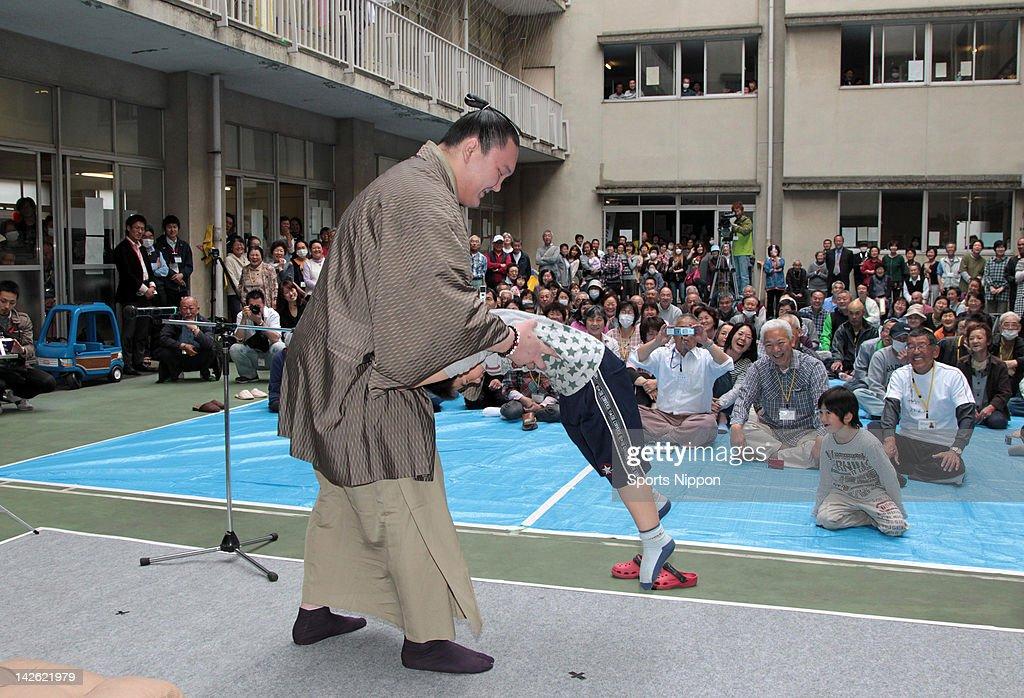 Yokozuna, sumo grand champion Hakuho play sumo with evacuated child from Futaba City, inside the exclusion zone of the troubled Fukushima Daiichi Nuclear Power Plant on June 1, 2011 in Kazo, Saitama, Japan.