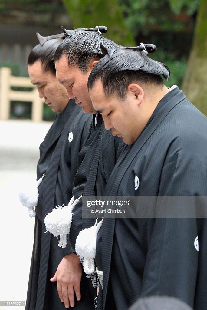 Yokozuna sumo grand champions Harumafuji Hakuho and Kakuryu pray before the 'Dohyoiri' ring purification ritual at Atsuta Jingu Shrine on July 5 2014...