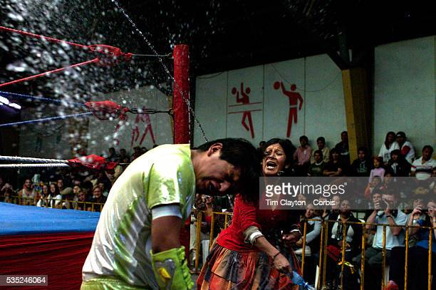 Yolanda La Amorosa throws water over her male counterpart as they fight out of the ring during the 'Titans of the Ring' wrestling group's Sunday...