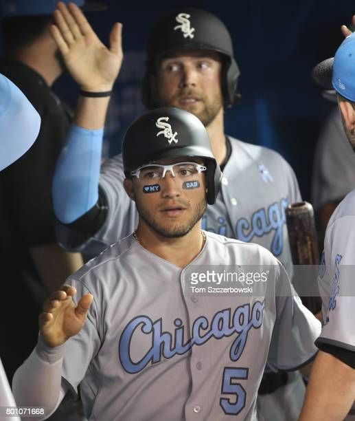 Yolmer Sanchez of the Chicago White Sox and Kevan Smith are congratulated by teammates in the dugout after both runners scored on a tworun single by...