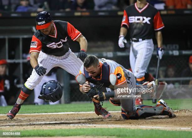 Yolmer Sanchez of the Chicago White Sox is tagged out at the plate in a collision with James McCann of the Detroit Tigers in the 7th inning at...