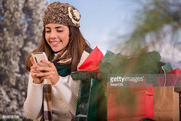 Yoman checks cell phone after Christmas shopping in winter.