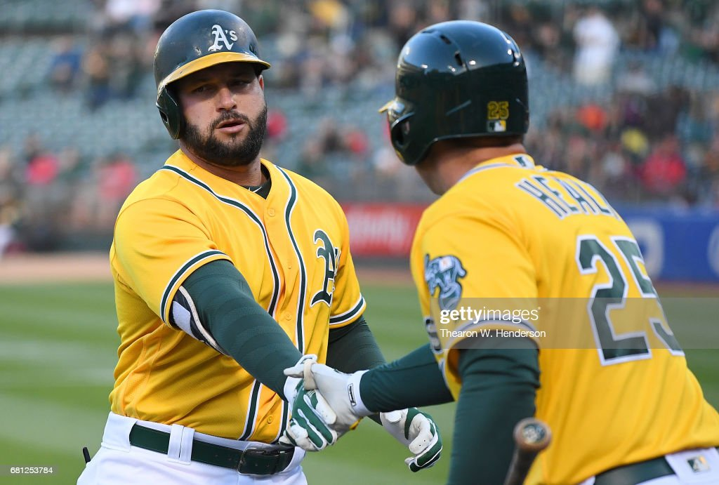 Yonder Alonso #17 of the Oakland Athletics is congratulated by Ryon Healy #25 after Alonso hit a two-run homer against the Los Angeles Angels of Anaheim in the bottom of the first inning at Oakland Alameda Coliseum on May 9, 2017 in Oakland, California.