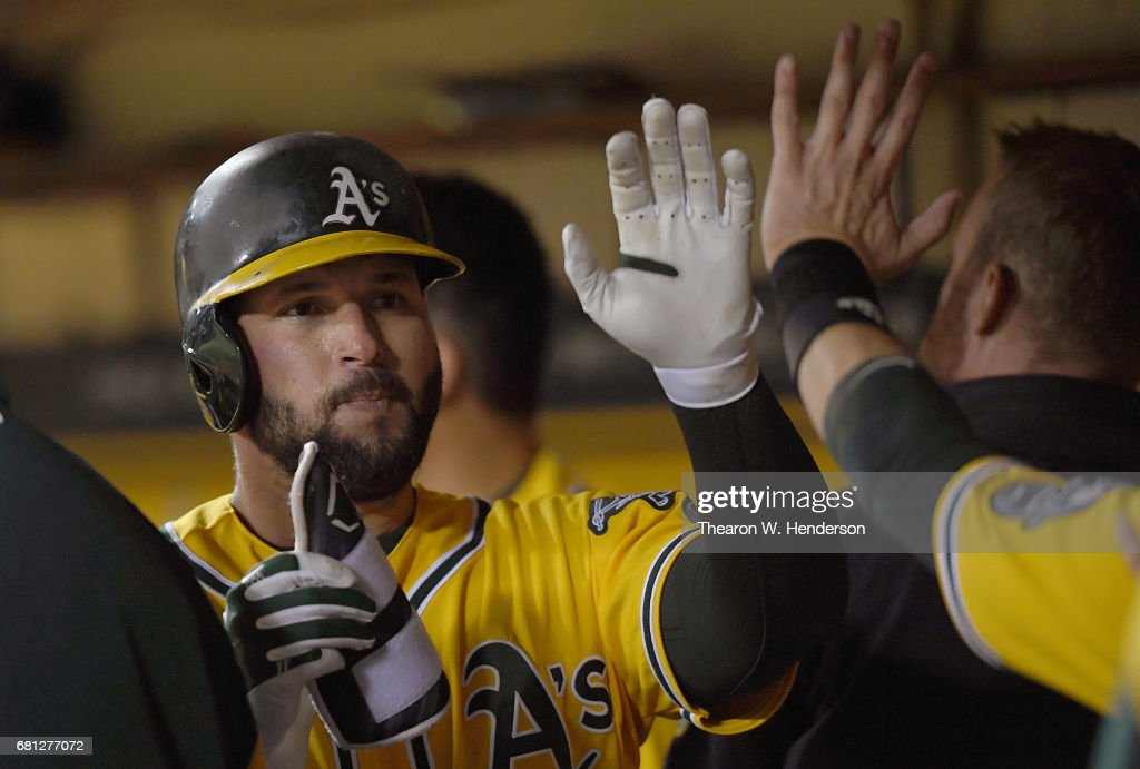 Yonder Alonso #17 of the Oakland Athletics is congratulated by teammates after hitting a solo home run against the Los Angeles Angels of Anaheim in the bottom of the six inning at Oakland Alameda Coliseum on May 9, 2017 in Oakland, California. The home run was Alonso's second of the game.