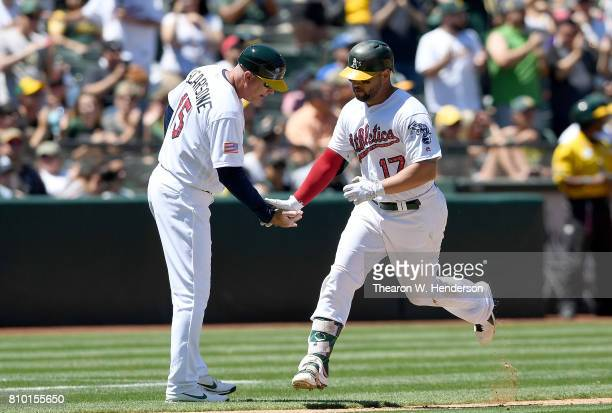 Yonder Alonso of the Oakland Athletics is congratulated by third base coach Steve Scarsone after Alonson hit a threerun homer against the Chicago...