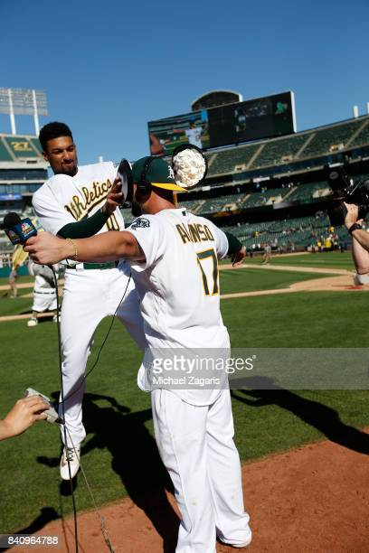 Yonder Alonso of the Oakland Athletics is congratulated gets pied by Marcus Semien after hitting a walkoff home run following the game against the...