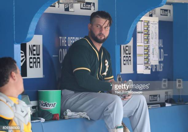 Yonder Alonso of the Oakland Athletics talks to Bruce Maxwell in the dugout as he reaches for chewing tobacco during MLB game action against the...