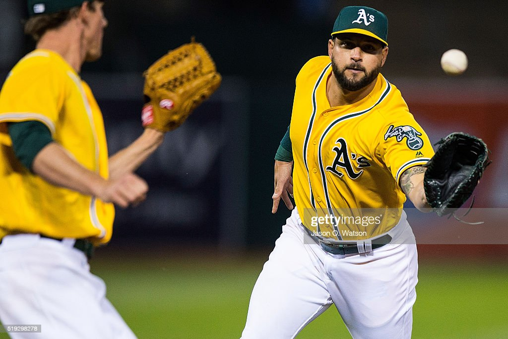 Yonder Alonso of the Oakland Athletics tosses the ball to Chris Bassitt after fielding a ground ball hit off the bat of Alex Avila of the Chicago...