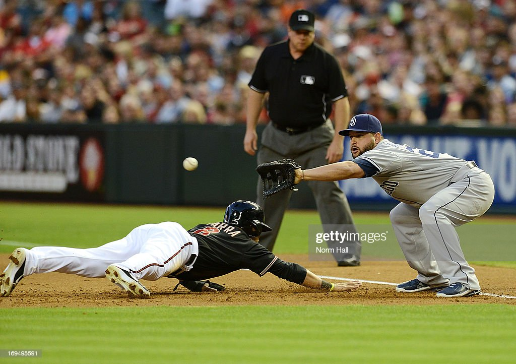 Yonder Alonso of the San Diego Padres catches a throw from the pitcher as Gerardo Parra of the Arizona Diamondbacks dives into first base at Chase...