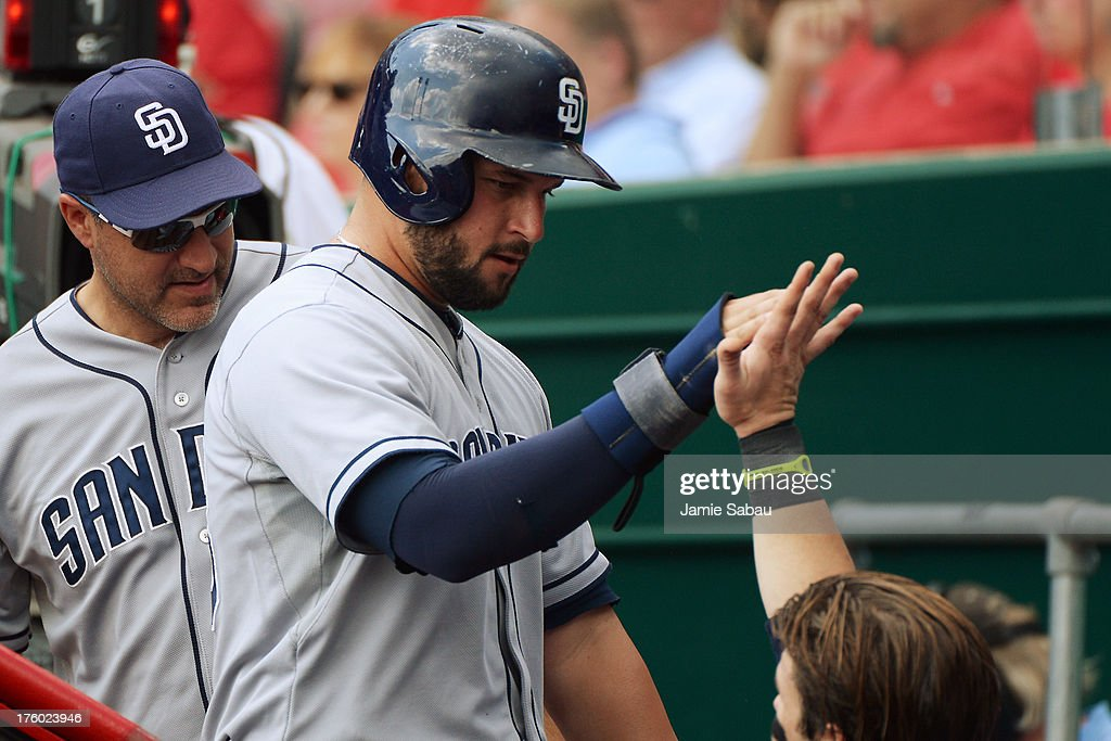 <a gi-track='captionPersonalityLinkClicked' href=/galleries/search?phrase=Yonder+Alonso&family=editorial&specificpeople=4424898 ng-click='$event.stopPropagation()'>Yonder Alonso</a> #23 of the San Diego Padres celebrates in the dugout with teammates after scoring the first run in the second inning against the Cincinnati Reds at Great American Ball Park on August 11, 2013 in Cincinnati, Ohio.