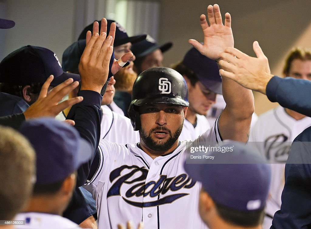 Yonder Alonso of the San Diego Padres is congratulated in the dugout after scoring during the third inning of a baseball game against the Texas...