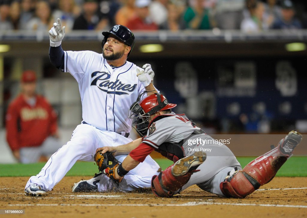 Yonder Alonso of the San Diego Padres is tagged out at the plate by Miguel Montero of the Arizona Diamondbacks during the fourth inning of a baseball...