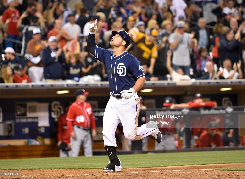 Yonder Alonso of the San Diego Padres points skyward after hitting a solo home run during the ninth inning of a baseball game against the Washington...