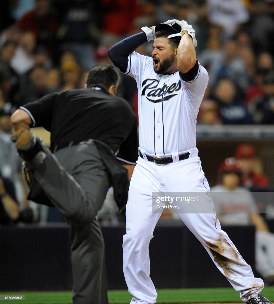 Yonder Alonso of the San Diego Padres reacts after being called out at the plate by umpire Mike DiMuro in the fourth inning of a baseball game...