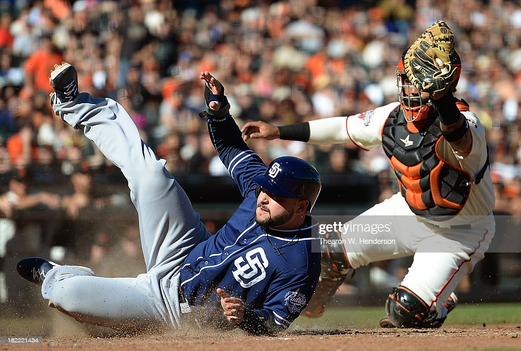 Yonder Alonso of the San Diego Padres scores sliding past the tag of Hector Sanchez of the San Francisco Giants during the ninth inning at ATT Park...