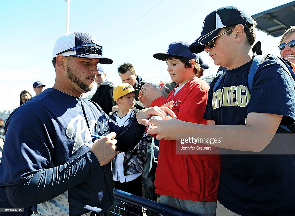 Yonder Alonso #23 of the San Diego Padres signs a ball for a fan prior to the spring training game against the Seattle Mariners at Peoria Sports Complex on February 24, 2013 in Peoria, Arizona.