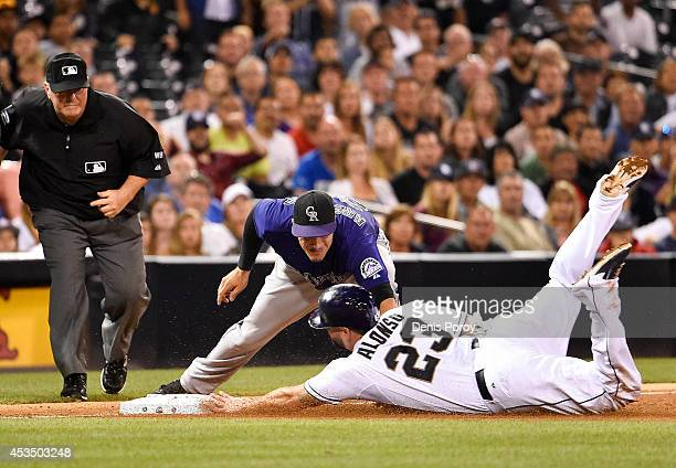 Yonder Alonso of the San Diego Padres slides into third base ahead of the tag of Nolan Arenado of the Colorado Rockies as umpire Dana DeMuth makes...