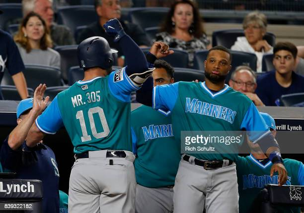 Yonder Alonso of the Seattle Mariners is congratulated by Robinson Cano after hitting a home run in the 11th inning of a game against the New York...