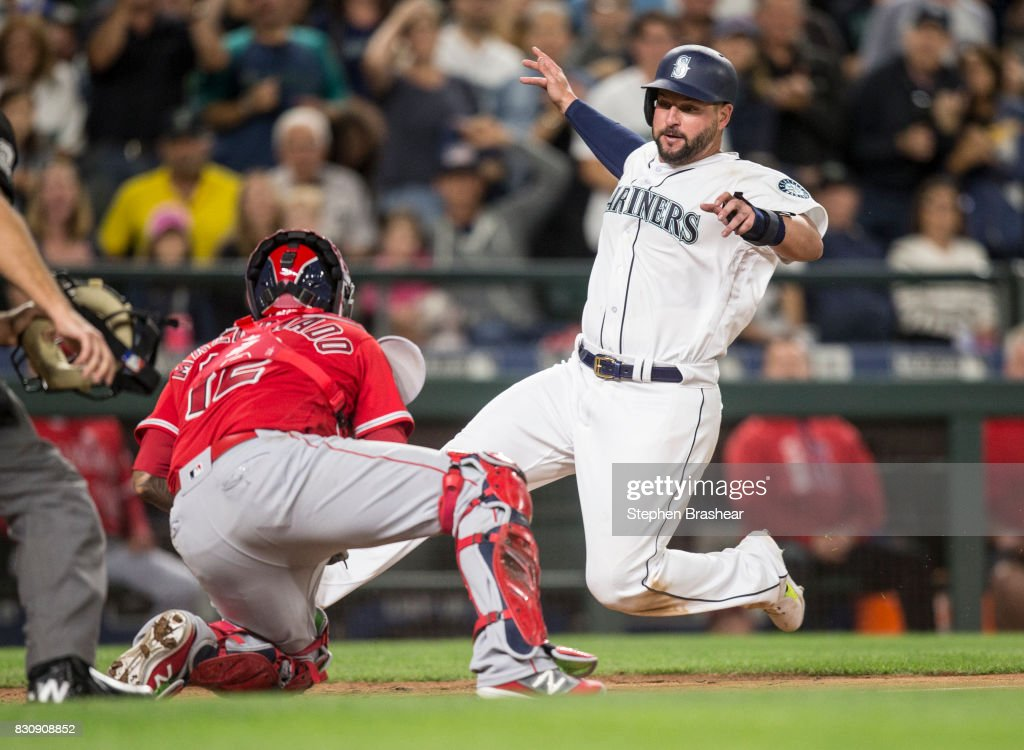 Yonder Alonso #10 of the Seattle Mariners is tagged by catcher Martin Maldonado #12 of the Los Angeles Angels of Anaheim as he slides into home plate on a double hit by Robinson Cano #22 of the Seattle Mariners during the seventh inning of a game at Safeco Field on August 12, 2017 in Seattle, Washington.