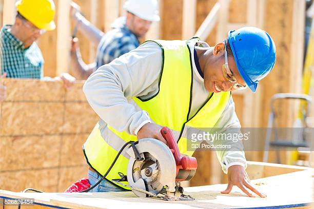 Yong African American man uses power tool at construction site