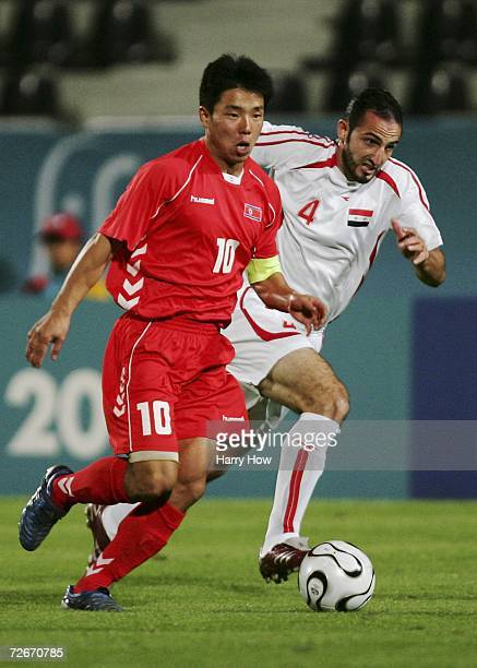 Yong Jo Hong of the Democratic People's Republic of Korea is pursued by Mohammad Istanbali of Syria during the Men's Football Round 2 Group F match...