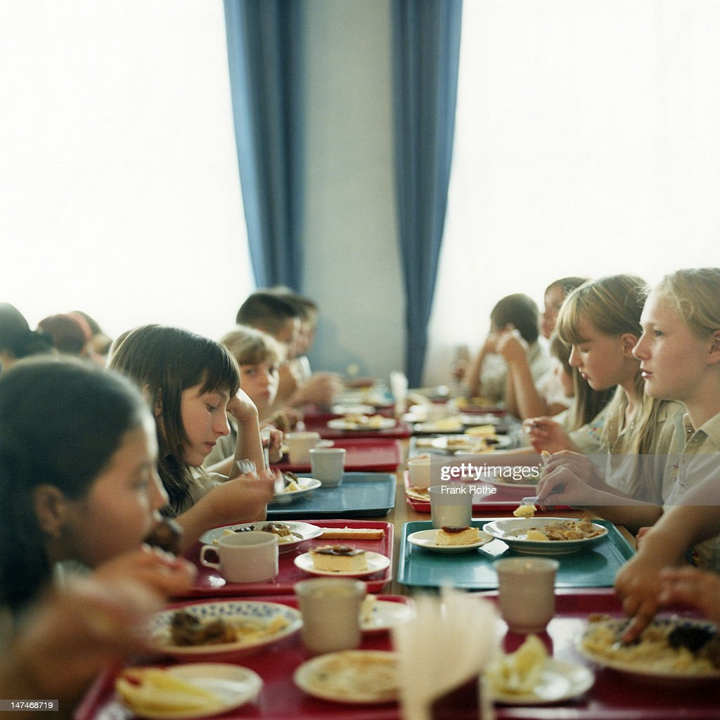 yong kids on a big table eating lunch together : Stock Photo