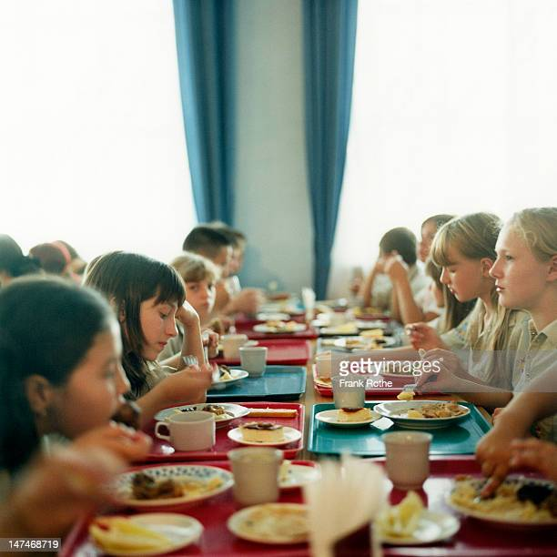 yong kids on a big table eating lunch together